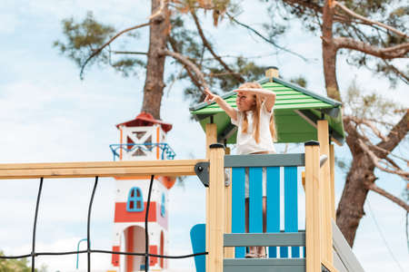 Children's games. A little girl looks intently into the distance and points at something with her hand, standing on a wooden game tower.