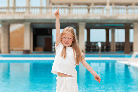 Emotions. The sweet girl raised her hand with a smile, pointing to the sky or attracting attention. The pool is in the background. Standard-Bild