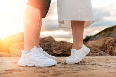 Couple kissing. Legs close-up. Sunset in the background. Valentines day concept.