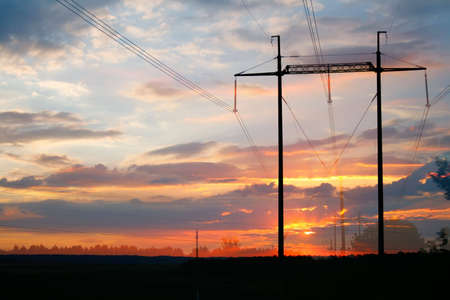 Electric lines against the sky painted by a sunset photo