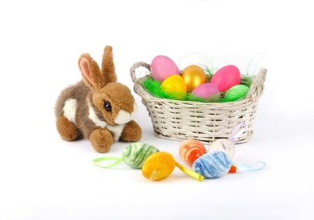 Easter - Fluffy bunny and basket with painted eggs  Isolated on a white background  Fluffy bunny and basket with painted eggs photo