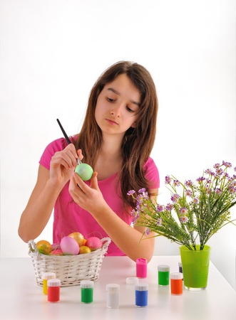 Girl painted Easter eggs isolated on a white background photo