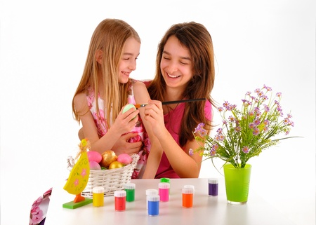 Two girls - sisters painted Easter eggs On the table is a basket with colored eggs, paint for coloring and a vase of flowers  Isolated on white background  photo