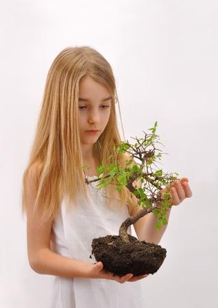 be dressed in: Child takes care of the tree Little girl dressed in white, holding in his hands a plant with soil - tree  The tree should be planted