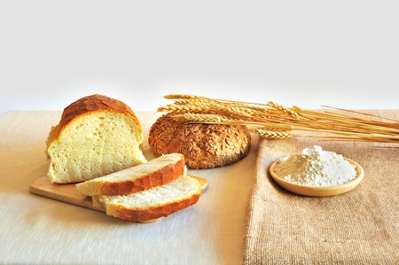 Bread,round loaf,ears of corn and bowl with flour on the table photo