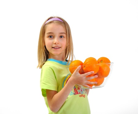 Little girl with oranges isolated on white photo