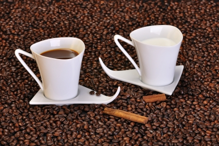 A cup of coffee, cup of milk and pieces of cinnamon on surface of coffee beans photo