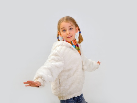 Little blonde girl in white winter coat, isolated on grey background  photo