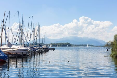 Lake Chiemsee, Bavaria, Germany - August 7th, 2016. Several sailing boats at a landing stage in Breitbrunn. In the background the well known Kampenwand.