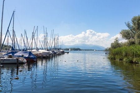 landing stage: Lake Chiemsee, Bavaria, Germany - August 7th, 2016. Several sailing boats at a landing stage in Breitbrunn. In the background the well known Kampenwand