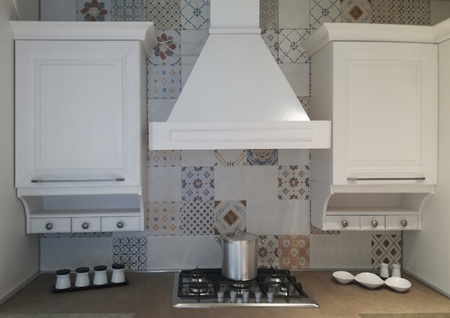 Detail cooking space in the kitchen - with stove, hood and white cabinets Фото со стока