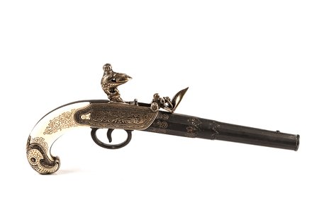 Flintlock pistol with engraved handle over a white background