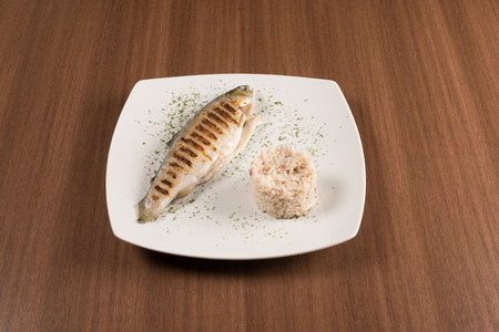 Grilled trout with rice on a with dish