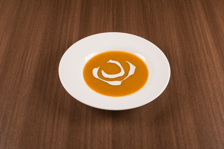 traditional pumpkin cream soup on a white background