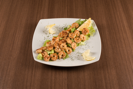 shrimp with salad and lemon on a white background