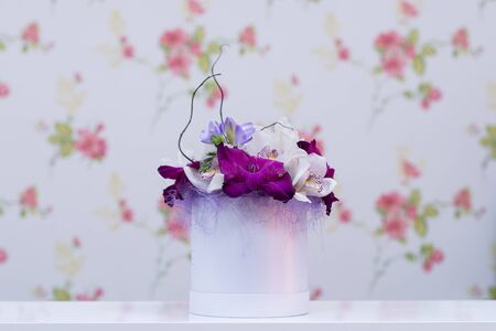 orchid arrangement on a white table with floral wallpaper in background