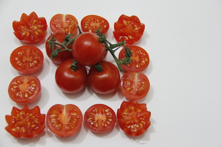 whole bunch of Piccadilly tomatoes inside a square of Piccadilly tomatoes cut in half Stock Photo