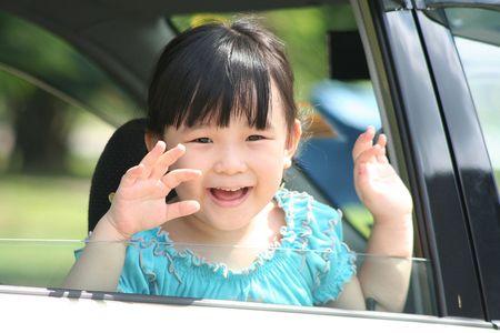Girl smiling & waving goodbye in a car. photo