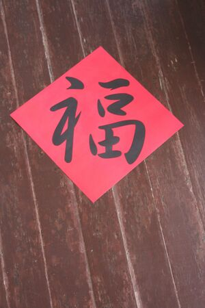 caligraphy: Chinese caligraphy for greetings during Chinese New Year, on wooden background. Stock Photo
