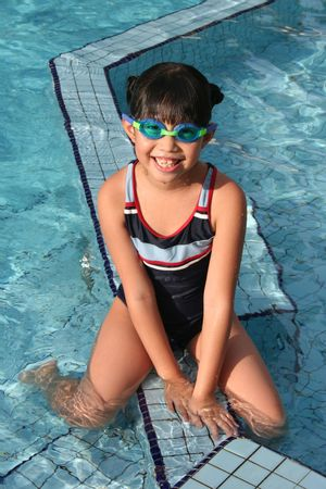 swimming costume: girl with swimming costume sitting at swimming pool