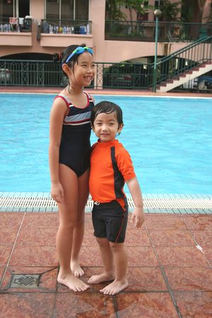 swimming costume: boy & girl with swimming costume at the pool