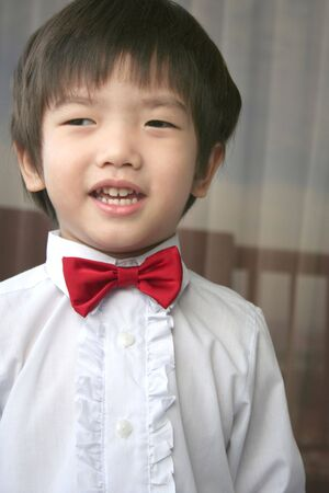 3 year old: 3 year old page boy with red bow-tie smiling Stock Photo