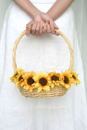 womans hand holding a basket of sunflower photo