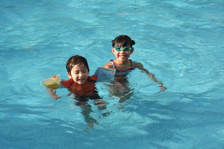 swimming costumes: girl & boy floating in the swimming pool
