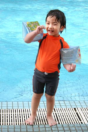Boy with arm floats & swimming costumes standing by the pool Stock Photo - 442029