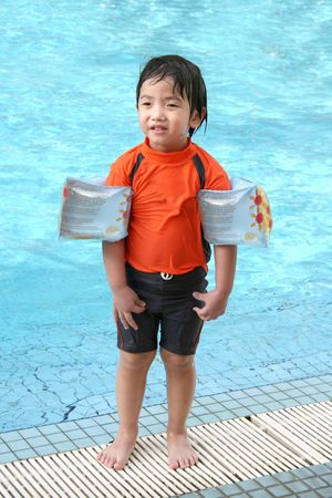 swimming costumes: Boy with arm floats & swimming costumes standing by the pool