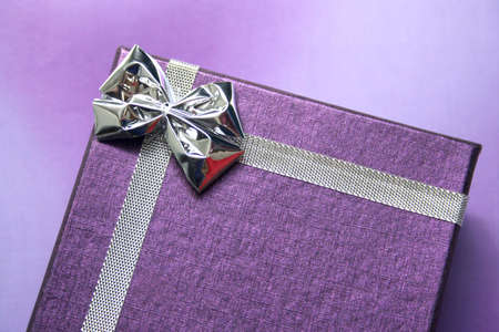 closed ribbon: purple gift box with silver ribbon on purple background