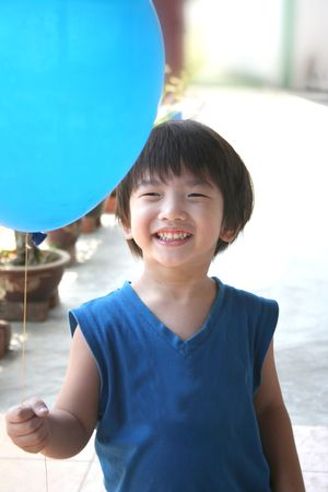 singlet: Boy with blue singlet holding blue balloon Stock Photo