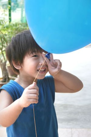 singlet: Boy with blue singlet holding blue balloon with victory hand sign