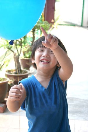 singlet: Boy with blue singlet holding & pointing at a blue balloon