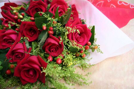 andamp: Roses bouquet wrapped in white andamp,amp, red Stock Photo