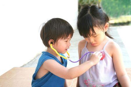 stethoscope boy: girl & boy playing toy stethoscope at leisure Stock Photo