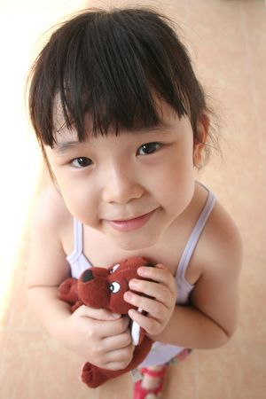 i kids: little girl smiling andamp,amp, holding brown toy doy