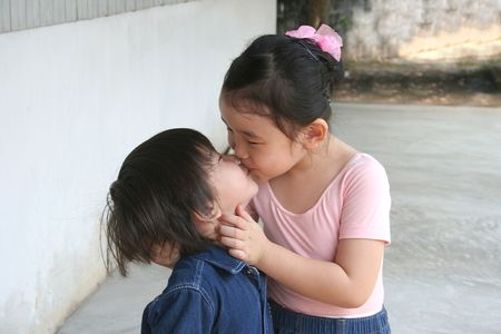 two companies: girl holding boys face & kissing
