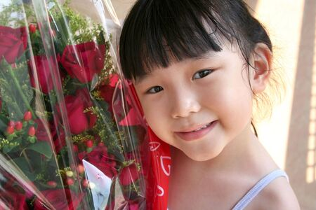 andamp: girl smiling andamp,amp, holding bouquet of red roses, wrapped with red wrapping paper Stock Photo