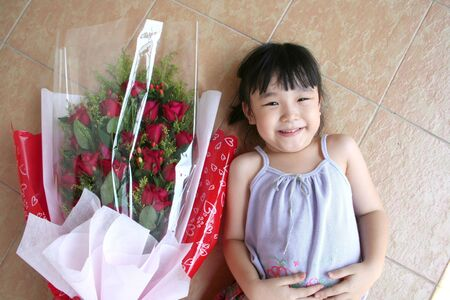 andamp: Girl andamp,amp, bouquet of red roses wrapped with red andamp,amp, white wrapper lying on the floor Stock Photo