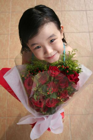 andamp: girl smiling, standing andamp,amp, holding bouquet of red roses Stock Photo