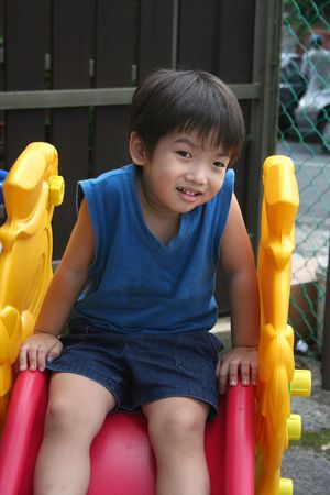 Little boy in blue singlet on the slide photo