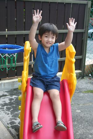 little boy in blue singlet waving both hands on the slide photo