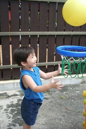 singlet: Little boy in blue singlet playing basket ball