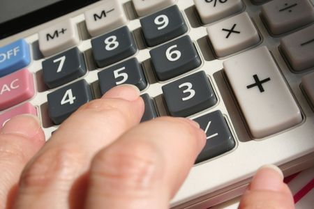 budgets: womans hand on calculator