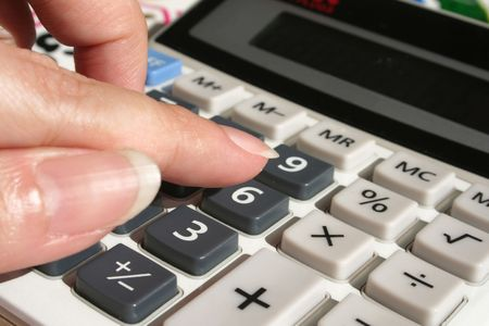 womans hand calculating on calculator photo