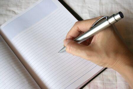 note book: Donna mano sulla nota scritta a penna libro  Archivio Fotografico