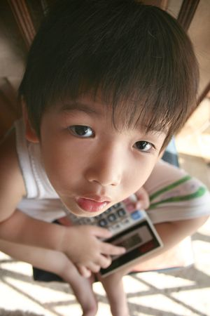 little boy holding calculator looking up photo