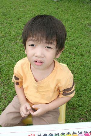 wondering boy sitting on little chair photo