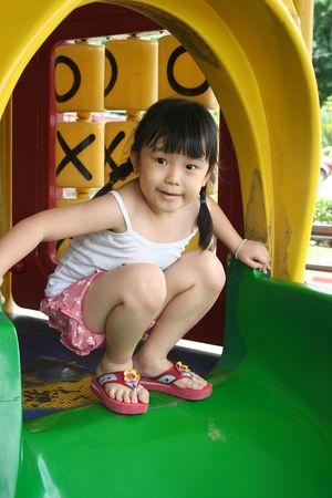 children playground: chica en cuclillas sobre la diapositiva  Foto de archivo